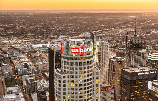 Los Angeles, California, USA - March 23, 2016:  Aerial view of the Us Bank Tower and sign in the Los Angeles downtown, Is visible also an helicopter flying around the tower. Image taken at sunset from a doorless helicopter.