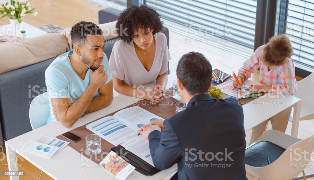 Banker consulting married couple in their home stock photo