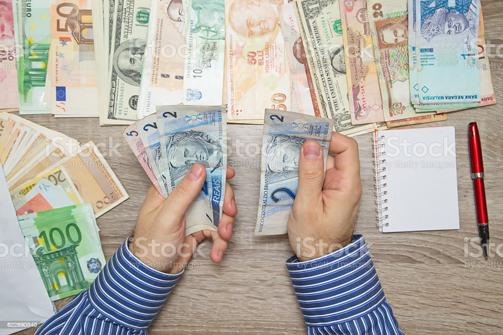 Banker counting Brazilian Real at his office table, World currencies stock photo