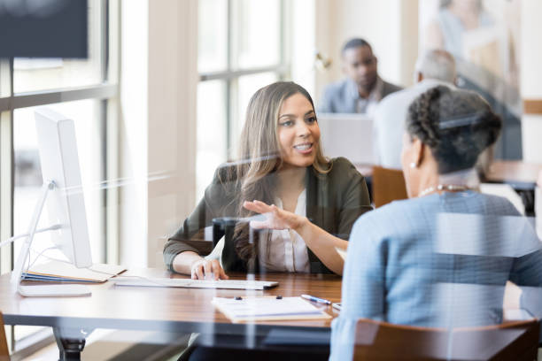 Banker discusses banking services to new customer stock photo