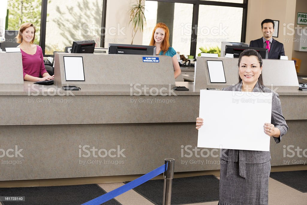 Banker with blank sign and happy tellers at the bank stock photo