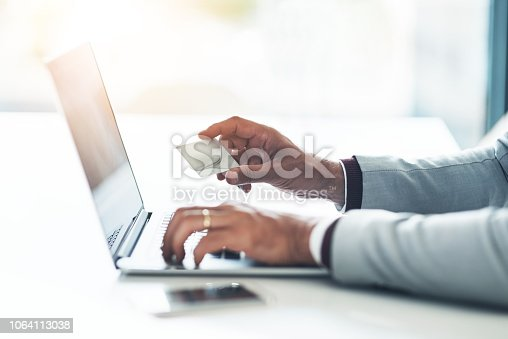 Cropped shot of an unrecognizable businessman holding his credit card while using a laptop at his desk