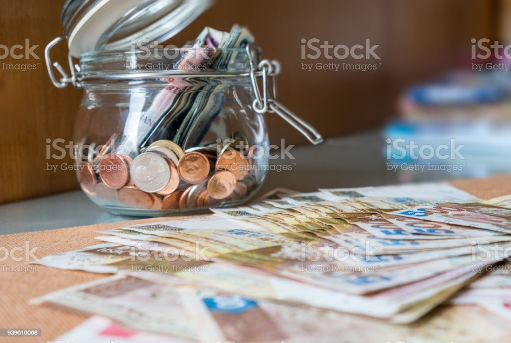 Banknote and coins in glass jar stock photo