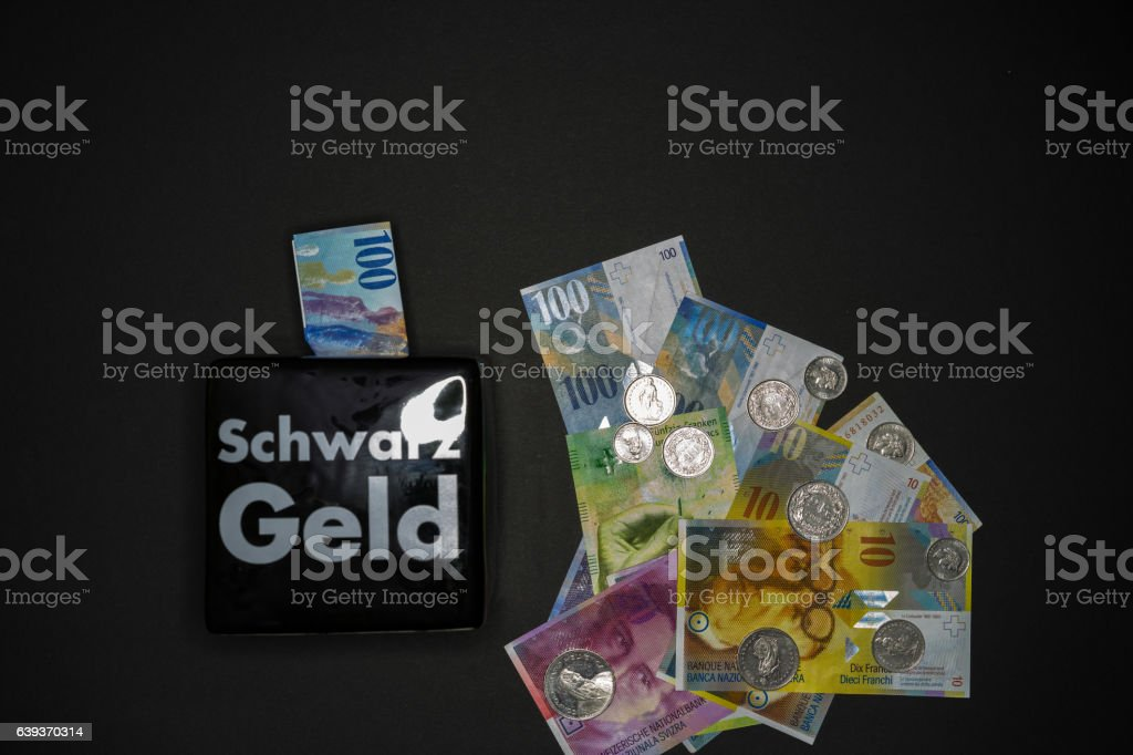 Banknotes and coins beside money box on black background stock photo