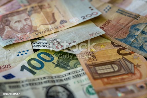 Banknotes in different currencies lie across each other. Dollar, euro, lekke, pesos. money.