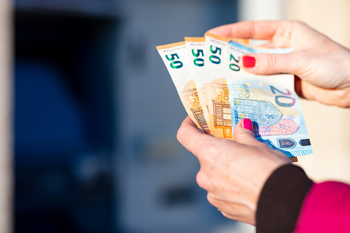 istock banknotes in the hands of a woman next to an ATM 1216439181