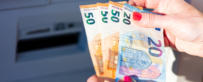 istock banknotes in the hands of a woman next to an ATM 1216439249