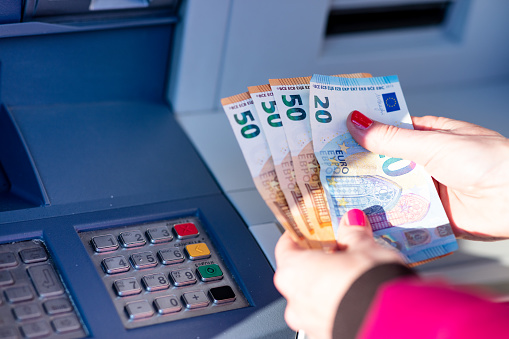 istock banknotes in the hands of a woman next to an ATM 1216439520