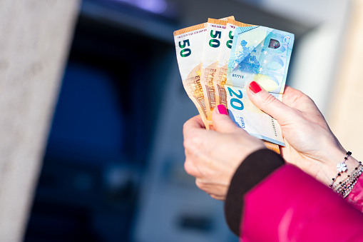 istock banknotes in the hands of a woman next to an ATM 1216439645