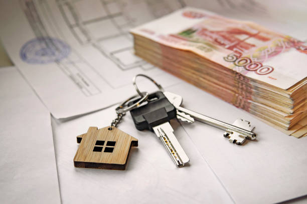 Banknotes of Russian rubles and keys to the apartment. Estate sale. The deal for the sale of apartment. Concept. stock photo