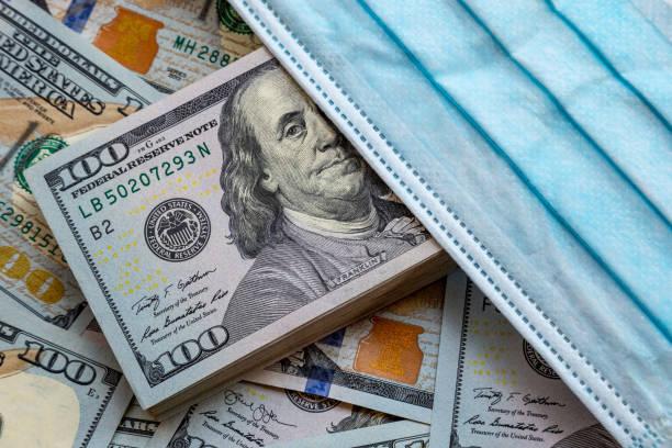 アメリカ合衆国の紙幣とウイルスに対する保護マスク。コロノウイルスに関連する世界経済危機。 - 金融と経済 ストックフォトと画像