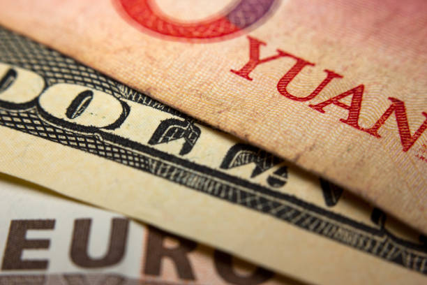 Banknotes Close-up of an Chinese yuan, an American dollar and a Euro banknote chinese currency stock pictures, royalty-free photos & images