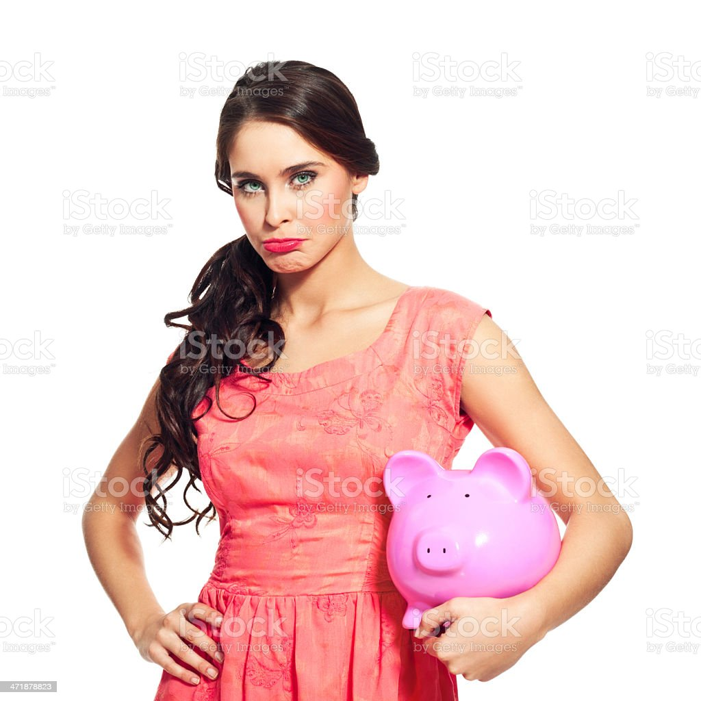Bankrupcy Worried young woman holding a pink piggybank and looking at camera. Studio shot, isolated on white. 20-24 Years Stock Photo