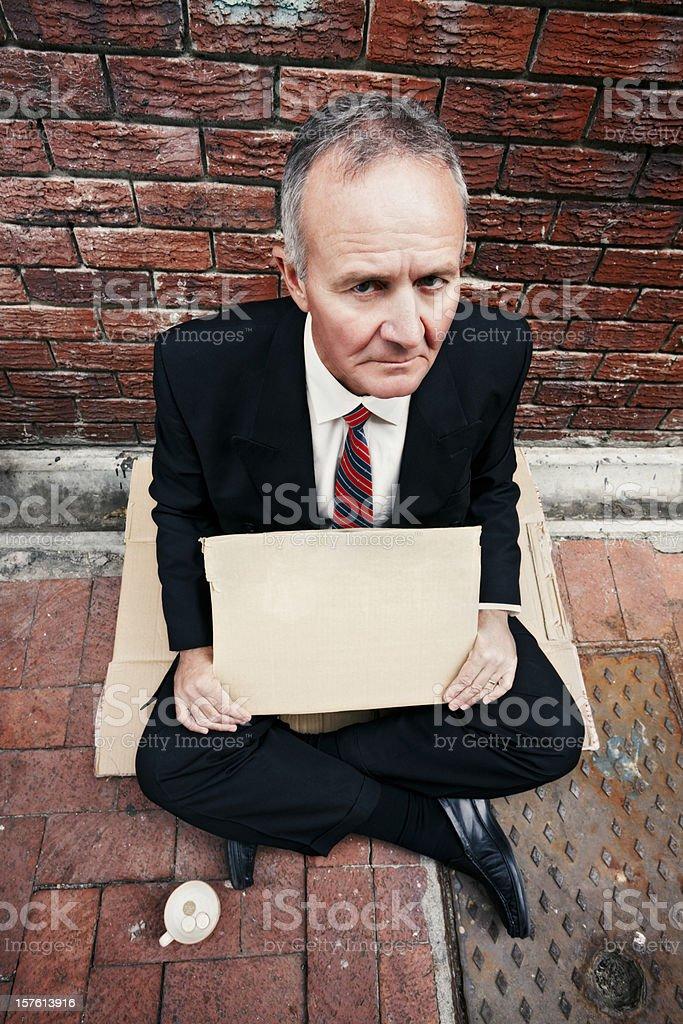 Bankrupt businessman begs royalty-free stock photo