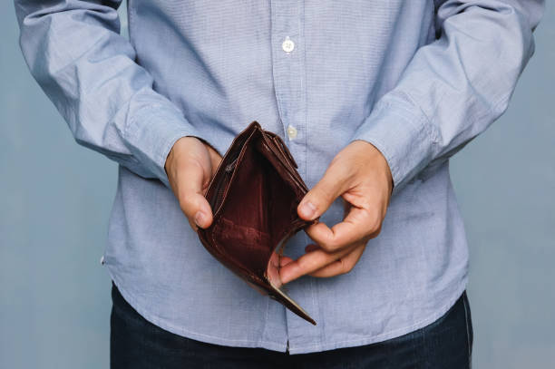 Bankruptcy - Business Person holding an empty wallet Bankruptcy - Business Person holding an empty wallet. Man showing empty wallet by showing the inconsistency and lack of money and not able to pay the loan and the mortgage. empty wallet stock pictures, royalty-free photos & images