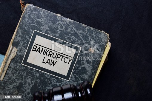 612372074 istock photo Bankruptcy Law book and gavel isolated on office desk. Law concept 1185185096