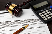 istock Bankruptcy petition for individuals with calculator and gavel. Concept of financial and unemployment crisis, personal debt, economy and recession. 1286514050