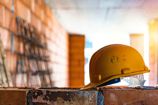 Yellow safety helmet or hard hat in construction site