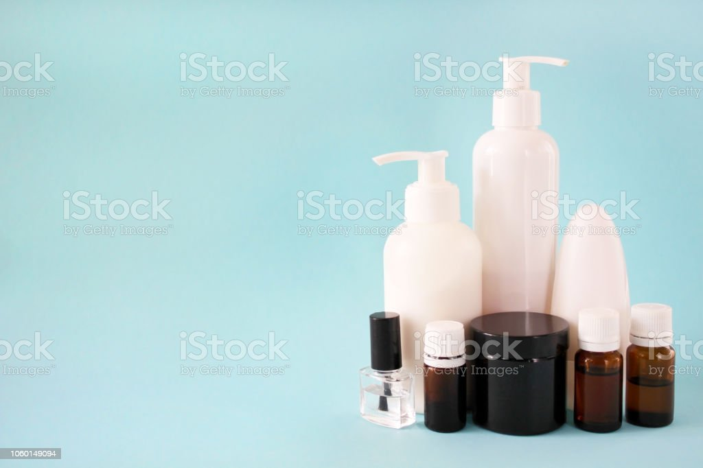 Banks and containers with cosmetics on a blue background. Cosmetic...