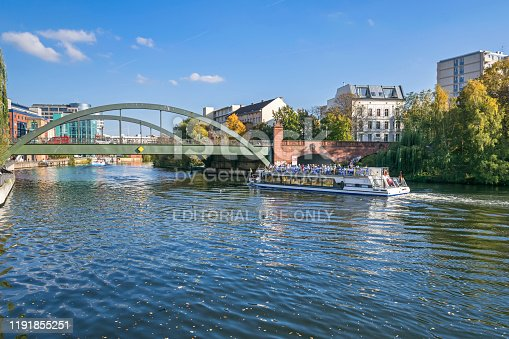 Berlin, Germany - October 14, 2019: Banks of the river Spree with a sightseeing boat and Lessing bridge, arch road bridge. View from Bundesratufer in a district Westphalian quarter