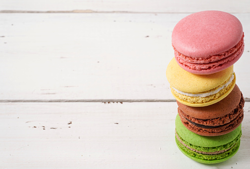 Banner. Four colorful green, pink, yellow and brown macaroons on white wooden rustic background. Copy space. Sweet And Colourful French cookies Macaroons. Selective focus.