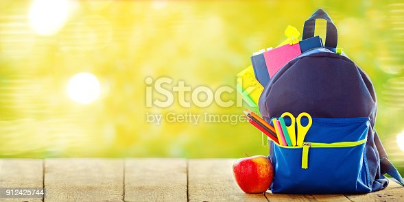 istock Banner. Full School backpack with apple on wooden and nature green background. 912425744
