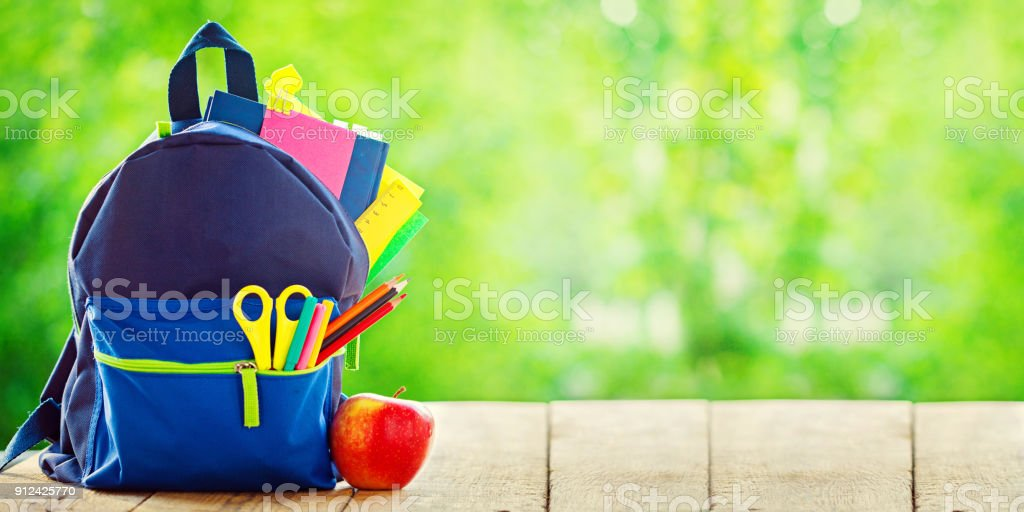 Banner. Full School backpack with apple on wooden and nature green background. stock photo