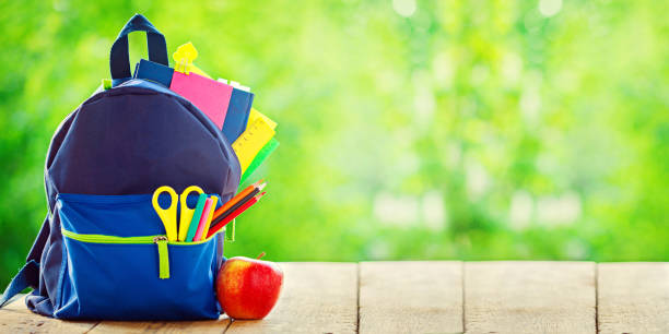 Banner. Full School backpack with apple on wooden and nature green background. - foto stock