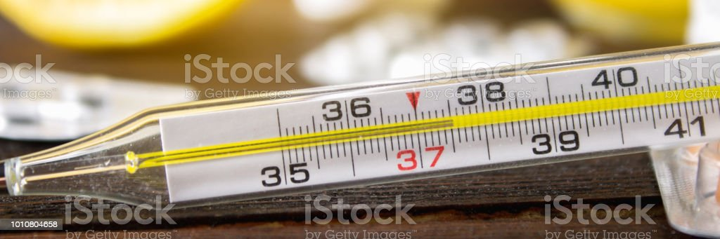 Glass mercury thermometer with a high temperature of 37.5 against the...
