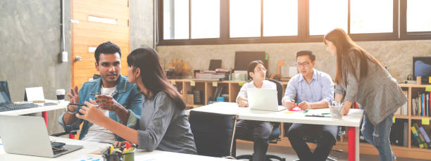 Banner of asian happy business creative team in routine work creative lifestyle sitting and talking together at modern office. Diverse teamwork or employee brastorming concept. stock photo