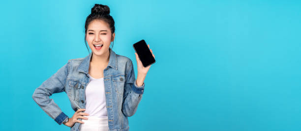 Banner of asian woman feeling happiness, blinks eyes and standing hold smartphone on blue background. Cute asia girl smiling wearing casual jeans shirt and connect internet shopping online and present stock photo