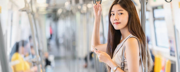 Banner of Asian woman passenger using social network via smart mobile phone in subway trainBanner of Young Asian woman passenger using social network via smart mobile phone in subway train when traveling in big city