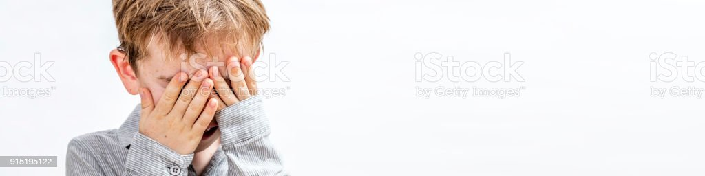 banner of boy covering his face for peekaboo or shyness stock photo
