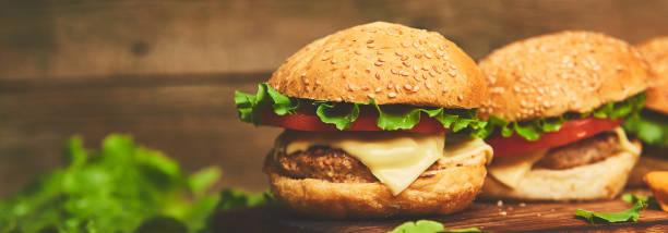 Banner von Craft Rindfleisch Burger auf Holztisch isoliert auf schwarzem Hintergrund. – Foto
