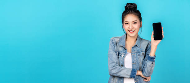 Banner of Happy asian woman feeling happiness and standing hold smartphone on blue background. Cute asia girl smiling wearing casual jeans shirt and connect internet shopping online and present stock photo