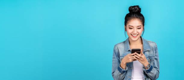 banner da feliz mulher asiática sentindo felicidade e digitando smartphone em fundo azul. garota asiática fofa sorrindo usando camisa jeans casual e conecta compras online e surfe na internet. - lifestyle color background - fotografias e filmes do acervo