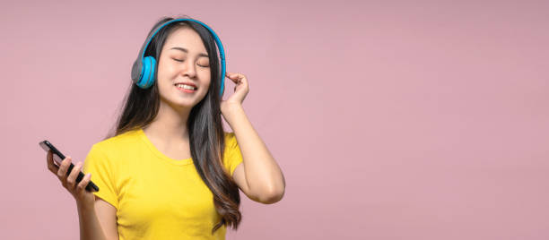 Banner of Happy chill asian girl listening to music in wireless headphone with smartphone. Woman listening podcast and wearing yellow shirt on pink isolated background. Banner of Happy chill asian girl listening to music in wireless headphone with smartphone. Woman listening podcast and wearing yellow shirt on pink isolated background. wireless headphones stock pictures, royalty-free photos & images