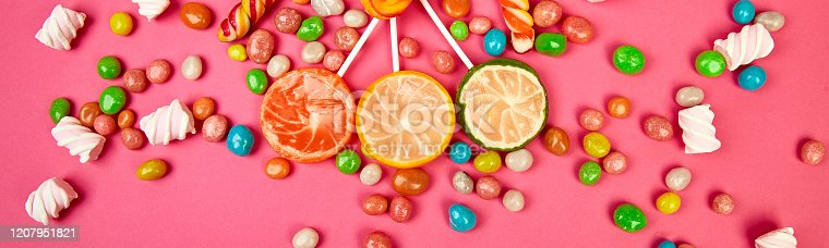 Banner of Ice cream waffles cones with colorful candy, sweets jelly, lollipop on stick, scattering of multicolored sweets on pink background. Flat lay, Top view. Copy space.