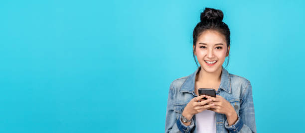 Banner of Portrait happy asian woman feeling happiness and looking camera holding smartphone on blue background. Cute asia girl smiling wearing casual jeans shirt and connect internet shopping online stock photo