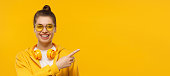 istock Banner of young laughing girl wearing headphones around neck, pointing right, isolated on yellow background 1256944019