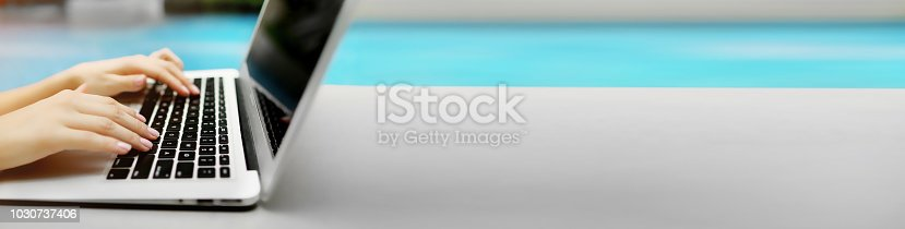 istock Banner with copyspace in grey color of laptop and female hands, blue background 1030737406