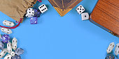 Banner with tabletop role playing items like blue and white RPG dices, character sheet and rule books with empty copy space on blue background in middle