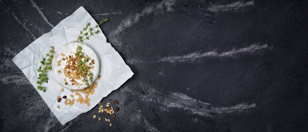 banner with top view on gourmet appetizer of white brie cheese or camembert with kitchen herbs and nuts - baked brie stock photos and pictures