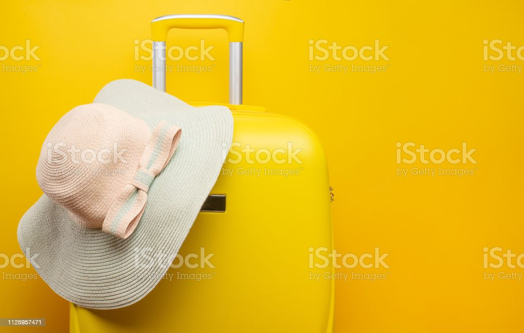 Banner yellow suitcase, with a hat for recreation, the beach. Travel...