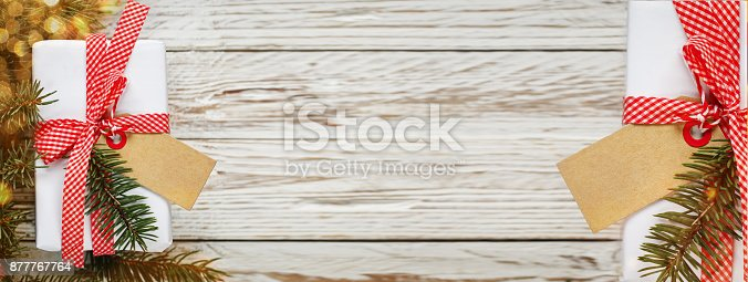 istock Banner.Holiday gift box. Christmas present with tag at white wooden table. Design copy space. 877767764