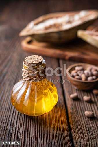 Baobab seed oil in glass bottle for healthy skin and hair on rustic wooden background