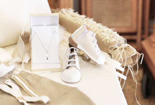 baptism baby clothes and cross stock photo