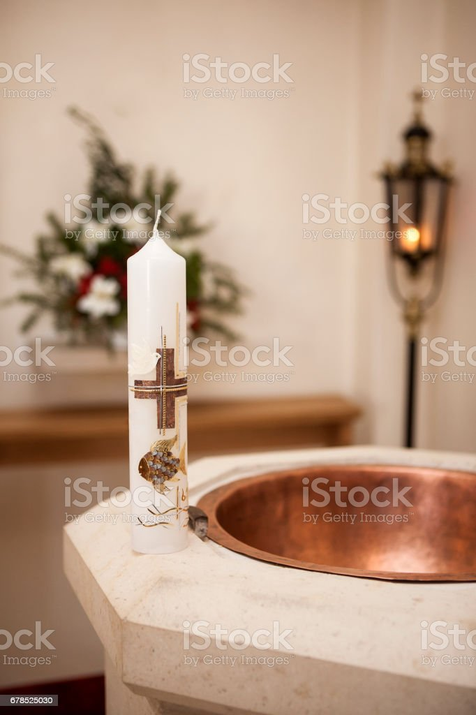 Baptismal candle on font stock photo