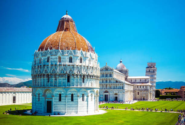 Baptistery of St. John on Square of Miracles, Leaning Tower, famous inclined tower of Pisa with green lawn in Pisa, Tuscany, Italy. Baptistery of St. John on Square of Miracles, Leaning Tower, famous inclined tower of Pisa with green lawn in Pisa, Tuscany, Italy pisa stock pictures, royalty-free photos & images