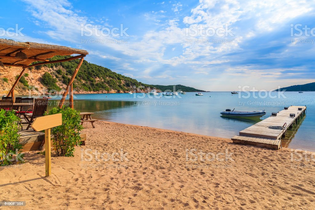 Bar and jetty on Santa Manza sandy beach in early morning light, Corsica island, France stock photo